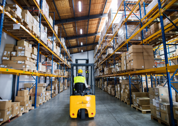 A man driving a forklift through a warehouse