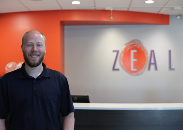 Trevor Weinrich standing in front of Zeal sign